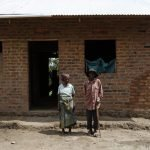 The same elderly couple in front of their new home, being built through the sale of their goat kids