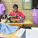 Sewing class is taken under the veranda - the teacher is creating templates for lesson plans.